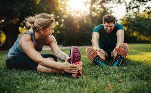 Couple stretching in the park before exercising in the morning