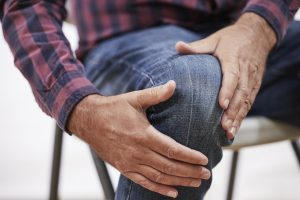Close Up Of Mature Man Suffering From Pain Or Arthritis Clutching Knee
