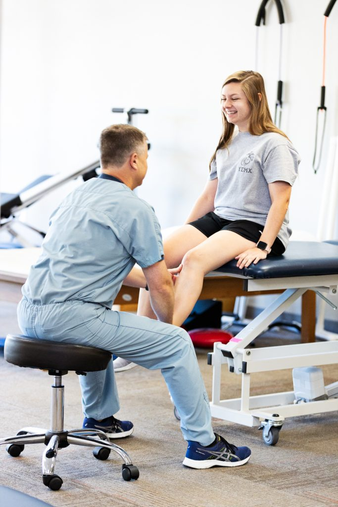 Physical Therapist working on patient with knee injury